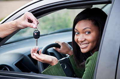 Dad handing over car keys to teenage driver