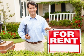 Man in front of for rent sign