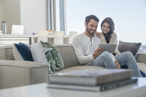 man and woman on tablet sitting on couch