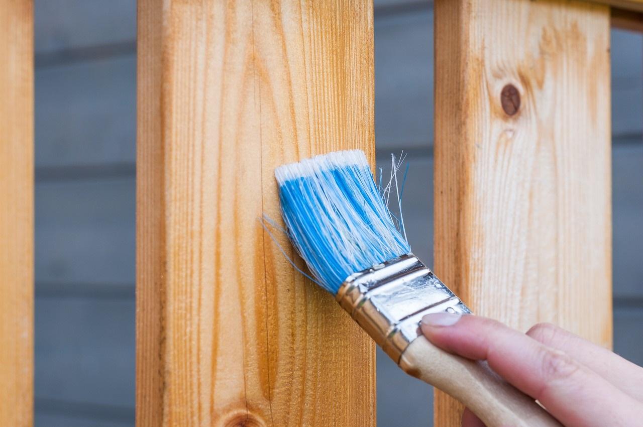 Paint brush painting on wood fence
