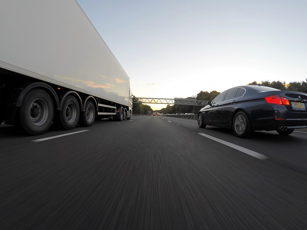 Semi-truck and car driving on a highway
