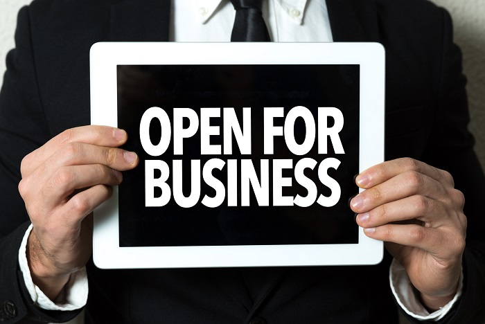 business man holding open for business sign on ipad