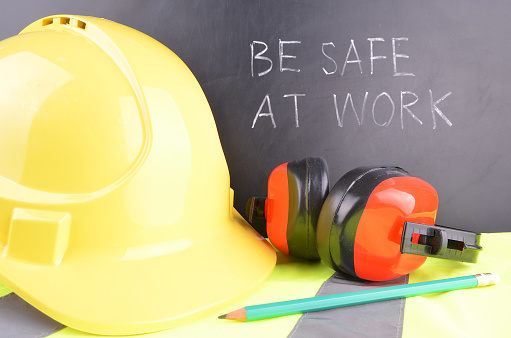 safety gear with sign behind saying be safe at work