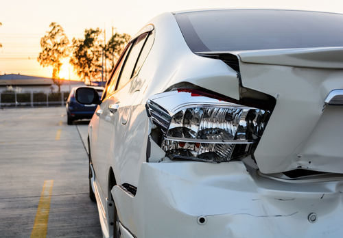 white car with damage to driver rear bumper