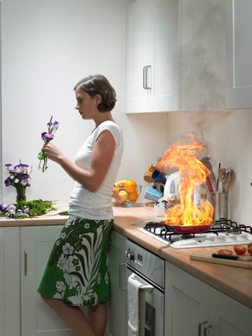 woman arranging flowers while there is a kitchen fire behind her