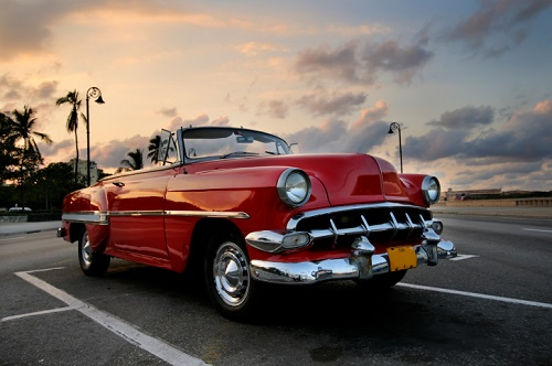 classic car parked in a parking lot at sunset