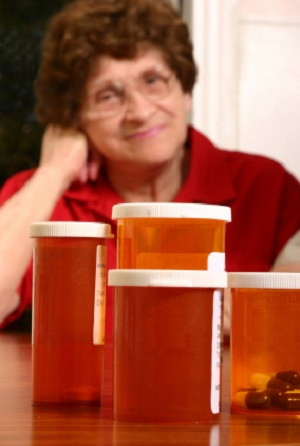 front view of multiple pill bottle obscuring view of older woman