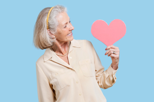 older woman holding paper cutout of heart