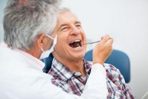 dentist working on older man's teeth
