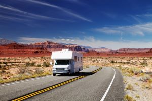 rv driving down the road in the desert